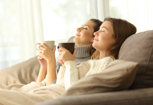 Two friends relaxing on a sofa with their eyes closed, holding mugs.