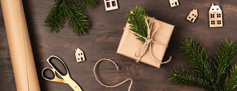 Gold scissors and string on the floor, with a present wrapped in brown paper and topped with string and a pine leaf. Surrounded by wooden house decorations.