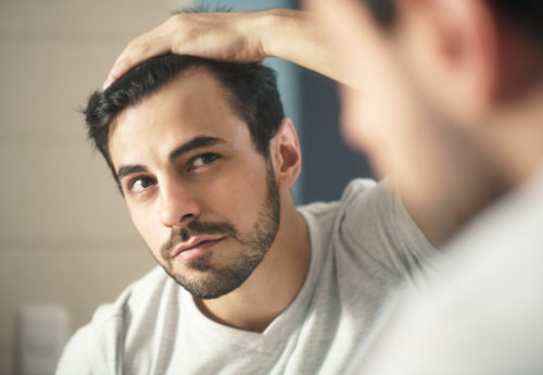 A man looking in a mirror, whilst pulling his hair back to look at his hairline.