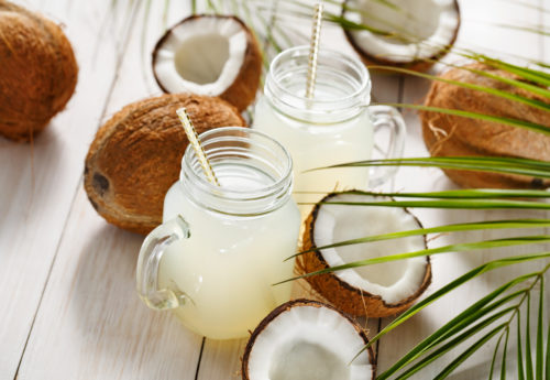 A variety of coconuts on a table with two mason jars filled with coconut water, with paper straws inside.