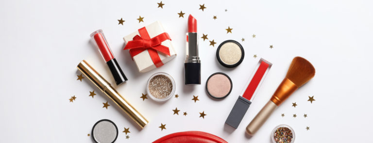 A red makeup back with various makeup prodcuts and stars surrounding it; including a gift box with a red bow attached.