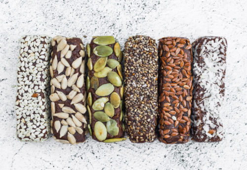 Vegan Protein bars lined up with varies nut and coconut topings.