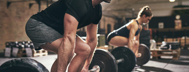 A man and lady in a squat position, getting ready to lift a bar with weights on either end.