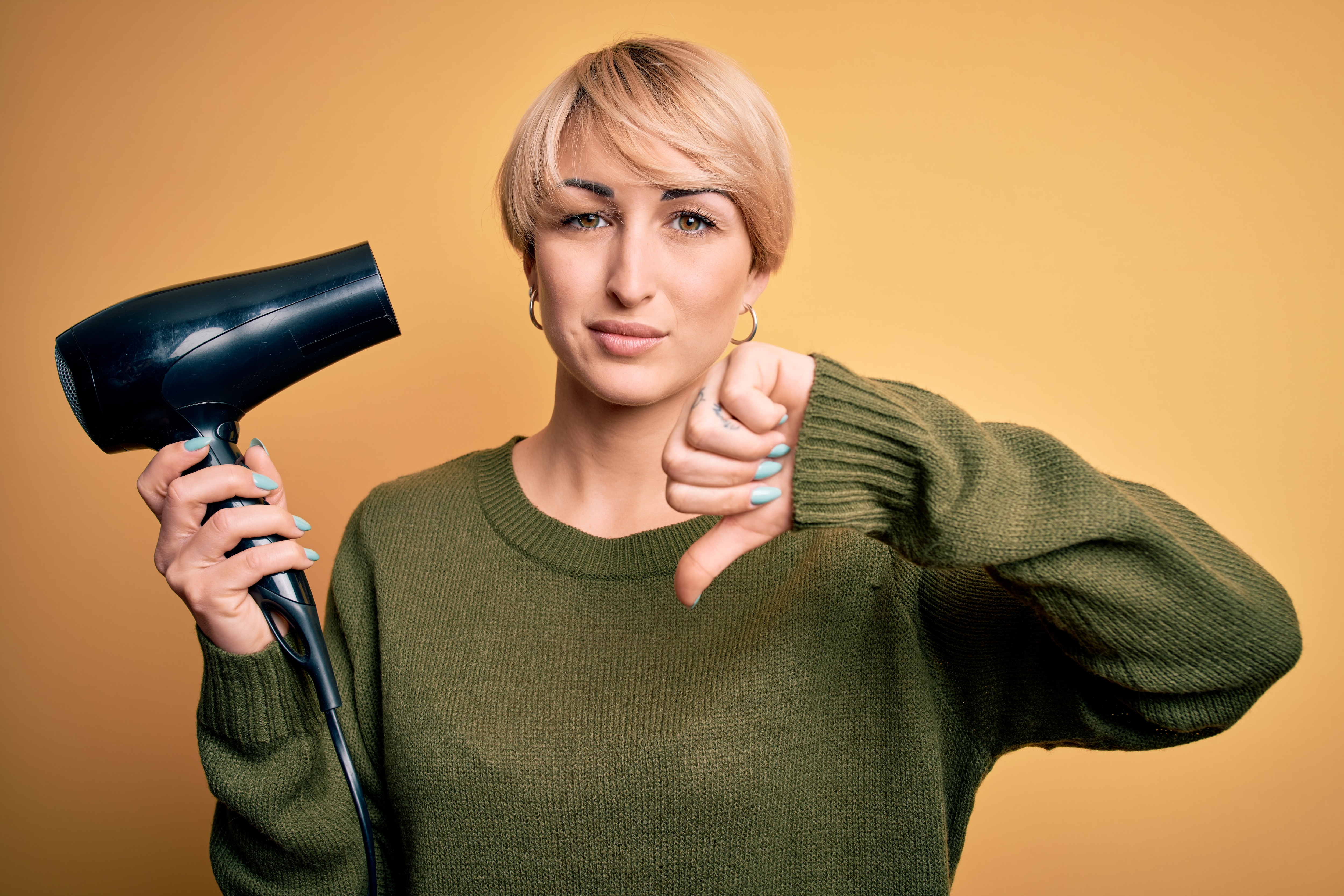 A lady with short hair, with her thumb down and a hair dryer in her other hand.