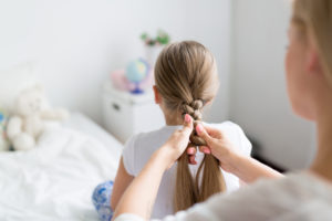 A lady plaiting a girls hair on a bed.